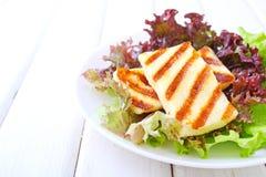 Grüner Salat mit gebratenem halloumi Käse in einer weißen Platte Lizenzfreies Stockbild