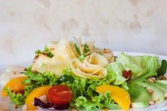 Grüner Salat mit Käse und Früchten auf Platte Stockfotografie