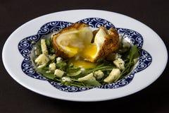 Grüner Salat mit Spiegelei und Käse auf einer weißen Platte Lizenzfreie Stockfotos