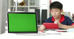 Grüner Schirm auf der Laptop-Computer und asiatischem Jungen, die auf Tablet-Computer auf Hintergrund aufpassen stock video
