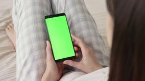 Grüner Schirm am Handy der jungen Frau im Bett zu Hause für Farbenreinheitsschlüssel stock footage