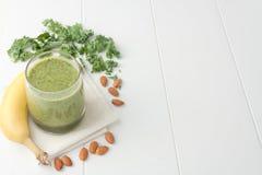 Grüner Smoothie, Bestandteile schließen Bananen, frischen Kohl und Mandeln mit ein Lizenzfreies Stockfoto