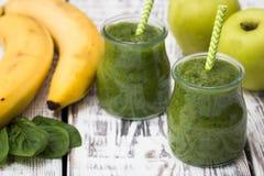 Grüner Smoothie mit Apfel, Banane und Spinat auf einem hellen Hintergrund Lizenzfreie Stockfotos