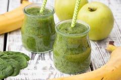 Grüner Smoothie mit Apfel, Banane und Spinat auf einem hellen Hintergrund Lizenzfreie Stockbilder