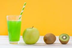 Grüner Smoothie mit Apfel und Kiwi auf einem weißen Holztisch- und Gelbhintergrund Lizenzfreies Stockbild