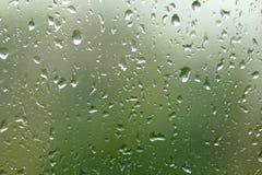 Grüner Sommerhintergrund von einem nassen Fenster mit Tropfen des Regens Dr. stockfotos