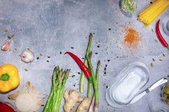 Grüner Spargel auf einem grauen Hintergrund Gesunde Bestandteile für Abendessenteller Gemüse, Geschirr, Tischbesteck, Teigwaren Lizenzfreie Stockfotos