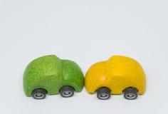 Grüner SpielzeugAutounfall zerschmetterte gelbes Spielzeugauto mit weißem Hintergrund und selektivem Fokus Lizenzfreies Stockbild