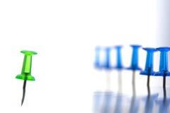 Grüner Stift vom links und ein Bündel blaue Stifte vom Recht Lizenzfreies Stockfoto