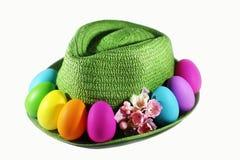 Grüner Strohhut mit bunten Eiern Ostern Stockfotos