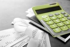 Grüner Taschenrechner mit Rechnungen und Notizbuch lizenzfreies stockbild