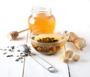 Grüner Tee in einem Glasteller, in einem Zucker, in einem Ingwer und in einem Honig auf weißem Hintergrund Stockfoto