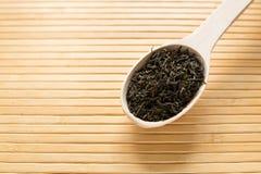 Grüner Tee in einem hölzernen Löffel auf einer hellen Bambustabelle Lizenzfreie Stockfotos
