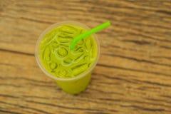 Grüner Tee Latte mit Eis in der Plastikschale und im Stroh auf hölzernem Hintergrund Selbst gemachter gefrorener Matcha-Latte-Tee stockbilder