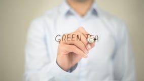 Grüner Tee, Mannschreiben auf transparentem Schirm Stockbilder