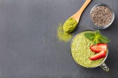 Grüner Tee Matcha chia Samenpudding, Nachtisch mit frischer Minze und Erdbeere auf einem gesunden Frühstück des schwarzen Schiefe stockfotografie