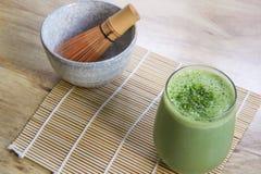 Grüner Tee Matcha Smoothie mit Steinschüssel und hölzerne wischen auf Bambusmatte auf Tabelle Lizenzfreies Stockfoto
