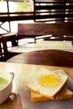 Grüner Tee mit Brotscheibe mit Orangenmarmelade Stockfoto