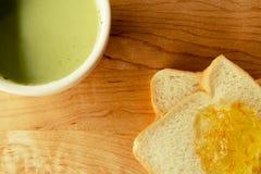 Grüner Tee mit Brotscheibe mit Orangenmarmelade Stockfotos