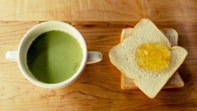 Grüner Tee mit Brotscheibe mit Orangenmarmelade Stockbilder