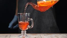 Grüner Tee mit Cup und Teekanne Heißer Tee, der in ein Glas auf Holztisch ausgelaufen wird Schwarzer Hintergrund Langsame Bewegun stock video