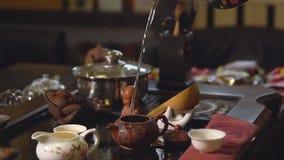 Grüner Tee mit Cup und Teekanne Teehersteller gießt kochendes Wasser in die Teekanne stock footage