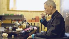 Grüner Tee mit Cup und Teekanne Trinkender Tee des Vorlagenmannes von einem weißen Becher stock video footage