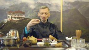 Grüner Tee mit Cup und Teekanne Vorlagenmann gießt grünen Tee von einer Glasteekanne in einen weißen Becher stock footage