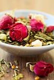 Grüner Tee mit Früchten, Gewürze, rosafarbene Blumenblätter Stockfotografie