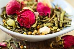 Grüner Tee mit Früchten, Gewürze, rosafarbene Blumenblätter Lizenzfreie Stockfotografie