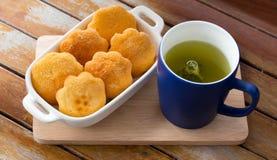 Grüner Tee und Eikuchen Stockbild