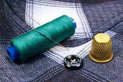 Grüner Thread auf einer Plastikspule mit Muffe und einem Knopf auf dem Hintergrund des Hemdes Lizenzfreies Stockfoto