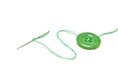Grüner Thread und Knopf auf Weiß Lizenzfreie Stockfotos