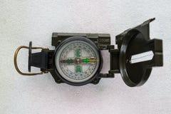 Grüner touristischer Kompass gelegen horizontal auf einem hellen Hintergrund stockfotografie