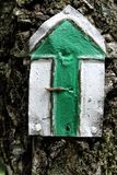 Grüner touristischer Zeichenpfeil auf dem Baum Stockbilder