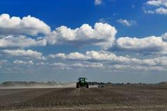 Grüner Traktor, der ein Feld mit blauem Himmel und Wolken auf Th kultiviert Stockbild