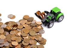 Grüner Traktor, der herauf Münzen harkt Stockfotos