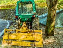 Grüner Traktor geparkt unter einem großen Schattenbaum Lizenzfreies Stockbild