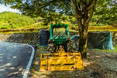 Grüner Traktor geparkt unter einem großen Schattenbaum Stockfotos