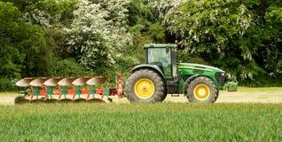 Grüner Traktor John Deere 7820, der einen Pflug zieht Stockbild