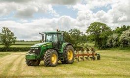 Grüner Traktor John Deere 7820, der einen Pflug zieht Stockbilder