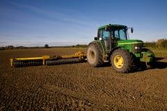Grüner Traktor mit Egge auf bebautem Feld lizenzfreie stockfotografie