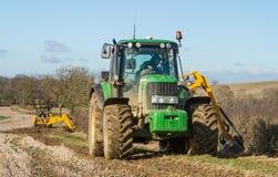 Grüner Traktorheckenausschnitt und -gräber, die einen Abzugsgraben klärt Lizenzfreie Stockfotografie