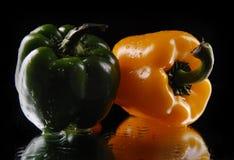 Grüner und gelber Gemüsepaprika auf einem schwarzen Hintergrund Stockfotografie