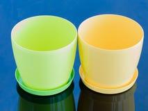 Grüner und gelber leerer Topf auf einer glatten Oberfläche Stockfoto