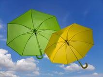 Grüner und gelber Regenschirm auf Hintergrund des blauen Himmels lizenzfreie stockfotos