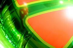 Grüner und orange Plastik-Ballon Stockfoto