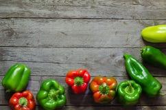 Grüner und roter Pfeffer auf hölzernem Hintergrund Lizenzfreie Stockbilder