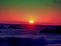 Grüner und roter Sonnenuntergang über Meer lizenzfreie stockfotos