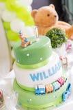 Grüner und weißer Geburtstags-Kuchen mit einer jährigen Kerze und Teddybären Stockbild